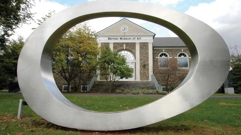 An artistic sculpture in an oval shape made of stainless steel before the Berman Museum of Art at Ursinus College.