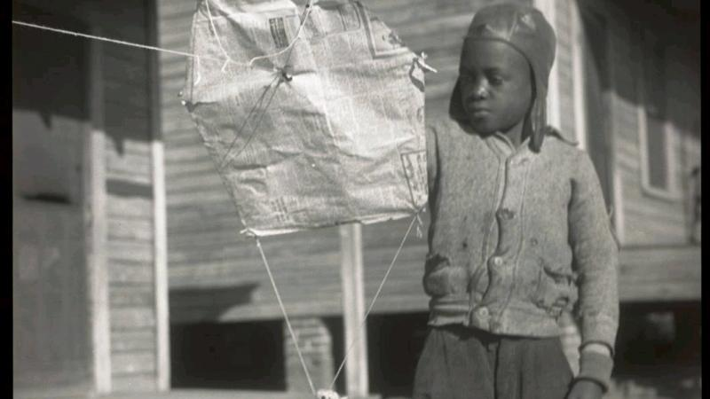 Black and white photo of an African American child playing with a kite.