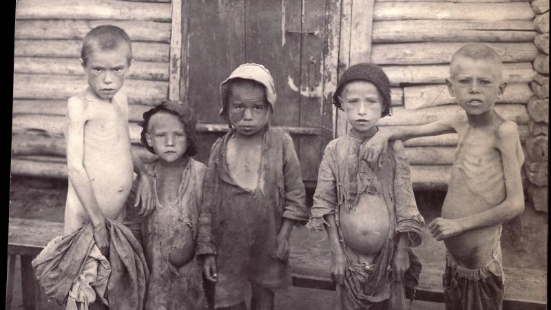 Five children, dressed in rags, stand in front of a wood doorway, stomachs bloated and ribs exposed