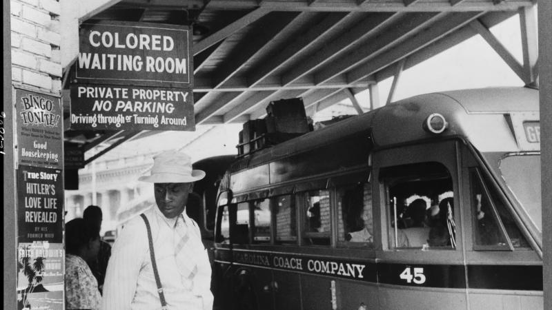 An African American man in a white hat heads toward the segregated waiting room while a bus idles at the curb
