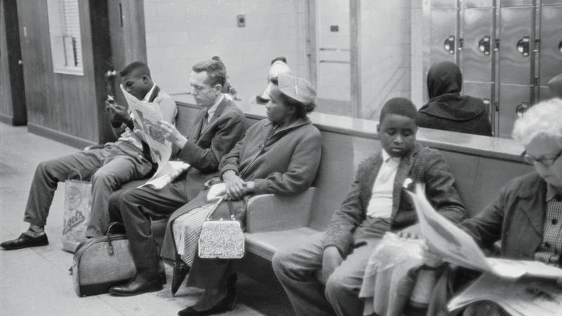 Black and white people sit on a bench next to each other while waiting for their bus
