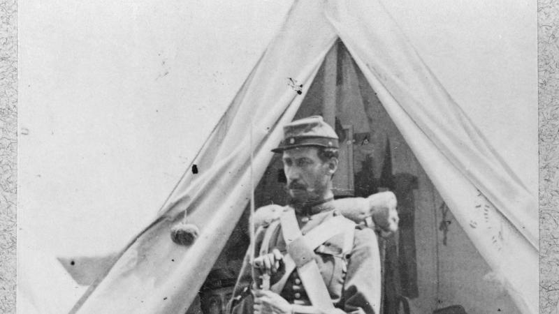 A soldier in full uniform, holding a bayonet, stands in front of a tent, where his fellow soldiers are sitting