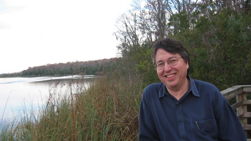 Hyde in a blue shirt, leaning on a railing overlooking a grassy pond
