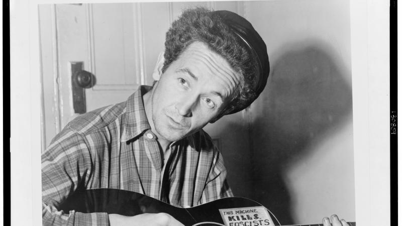 Guthrie in a plaid shirt, playing the guitar