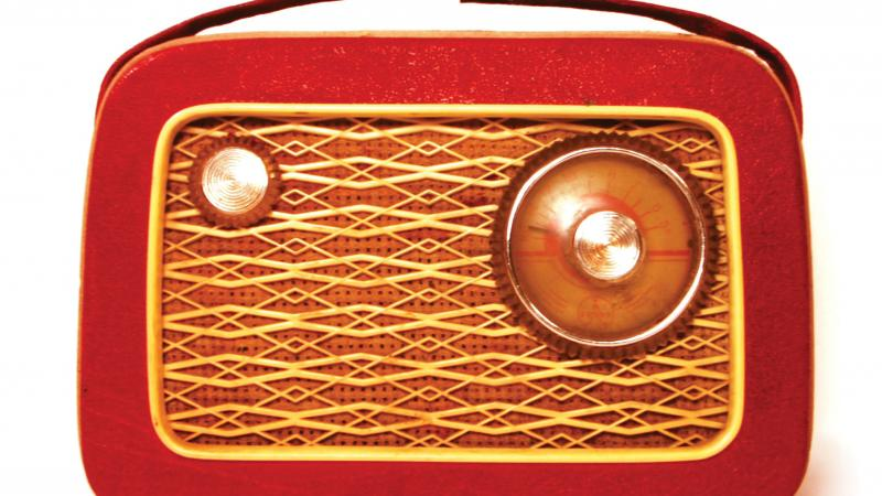 Red and wood-paneled radio, with a small handle attached to the top