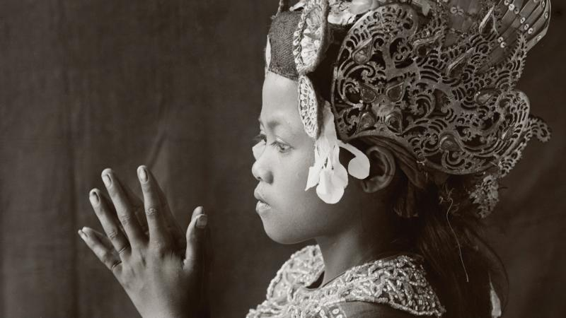 Side view of a young balinese dancer, palms clasped together, wearing a tall floral headdress and embroidered dress