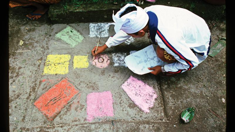 A priest kneels on the sidewalk, drawing