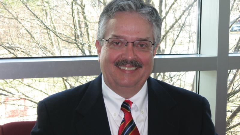 Paul Austin wearing glasses, wearing a red and blue striped tie and dark suit jacket