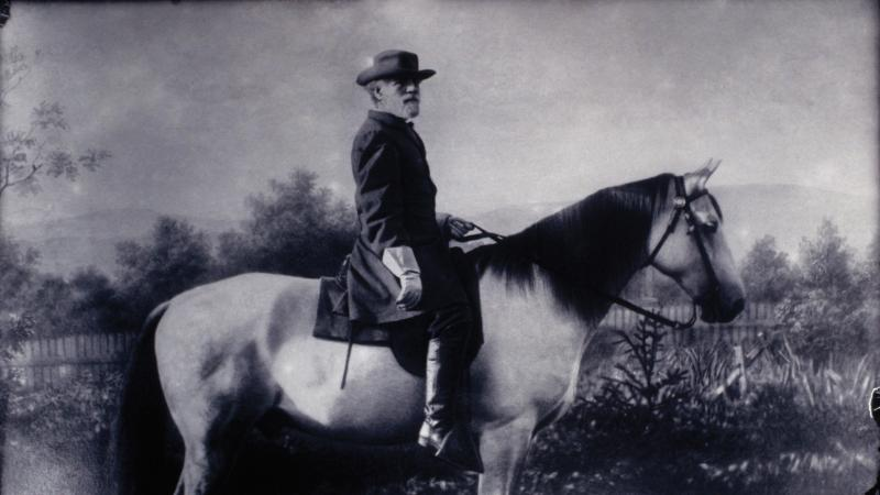Lee wearing a brimmed hat and black coat, astride a white horse with a black mane