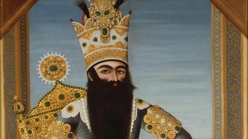 The Shah, with a long black beard, sitting on a richly decorated gold throne, wearing blue robes, gold jewelry, and a tall gold crown encrusted with gems