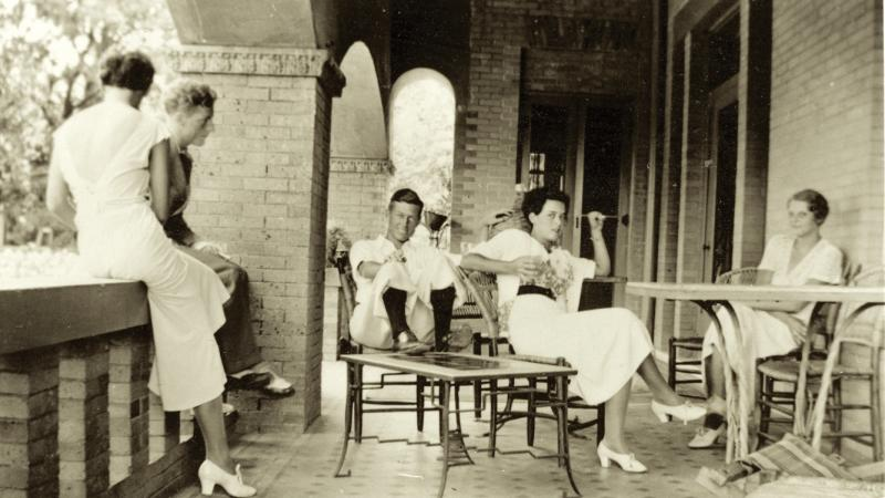 Reed, dressed in white, talking with her friends on the house terrace, sitting in lawn chairs