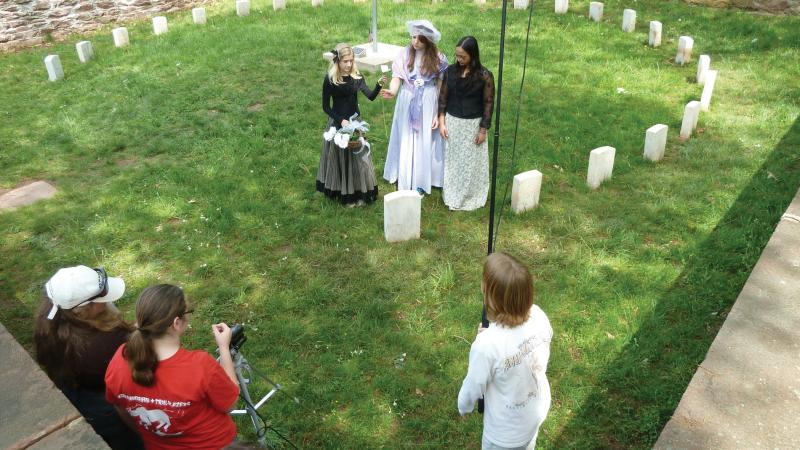 Photo of a group of young girls dressed in Civil War attire who are filmed in a small courtyard cemetery.