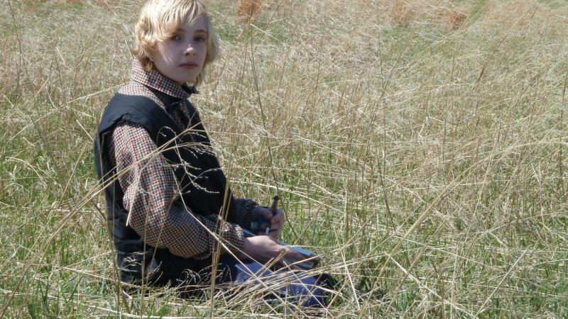 Photo of a young boy sitting in a field wearing a civilian outfit from the Civil War era.