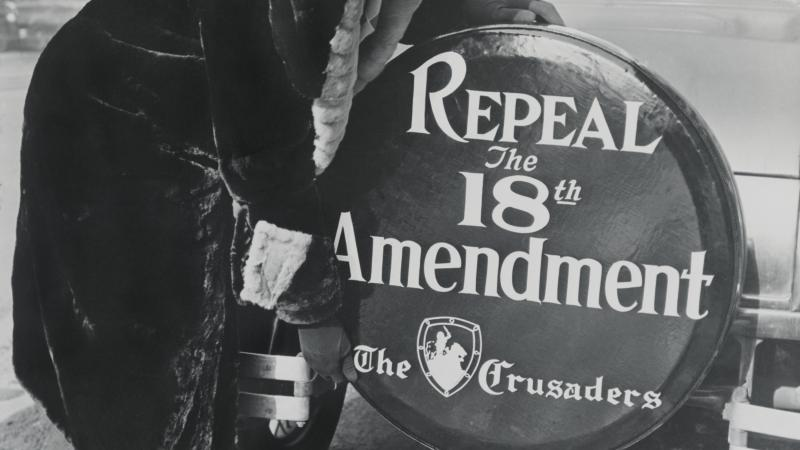 "Black and white photo of a woman standing before a spare tire cover, on the back of a car, that says, ""Repeal the 18th Amendment."""