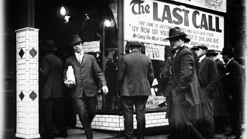 Black and white photo of men in formal attire heading into a liquor store. One man carries a packaged bottle in the foreground.