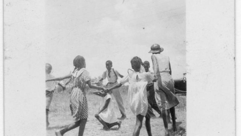 Black and white photo of African American children playing ring-around-the-rosie.