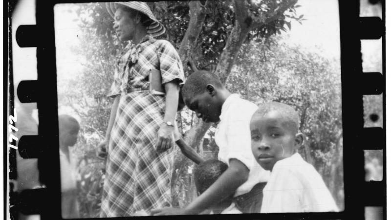 Black and white photo of a woman and three children under a shady tree.