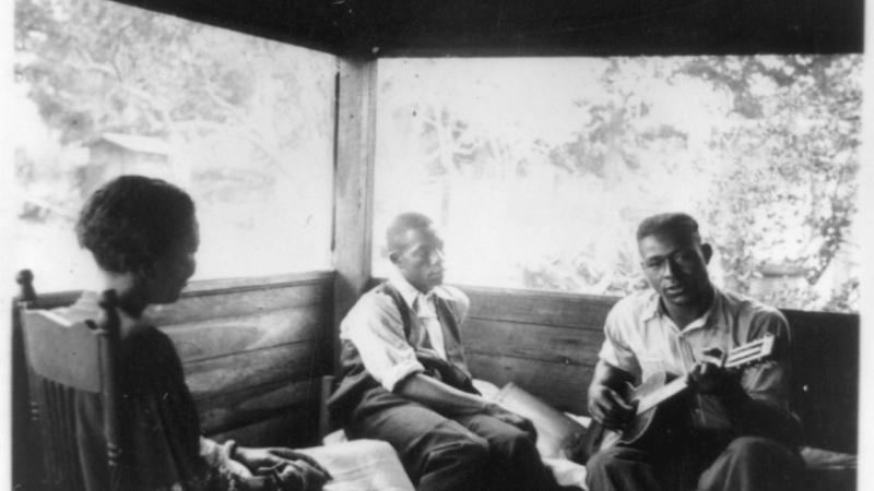 Black and white photo of three African Americans sitting on a porch, one of them playing the guitar.