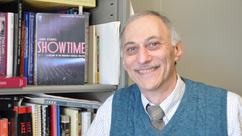 Color photo of Larry Stempel next to a bookcase, wearing a dark green vest, shirt, and tie.