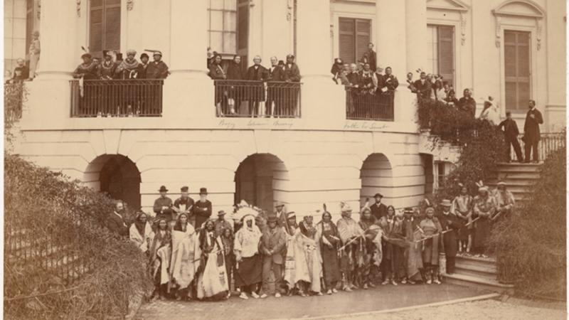 Sepia-colored photo of a large Native American delegation standing in front of the White House.