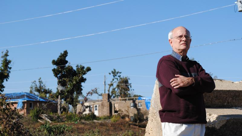 Color photo of Bob Stewart standing amid damaged houses.