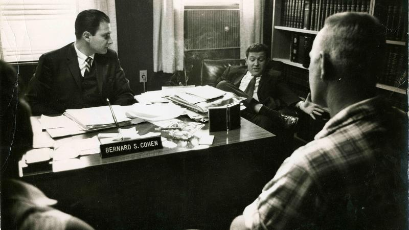 Black and white photo showing two lawyers behind a desk with the Loving couple seated in front of them.