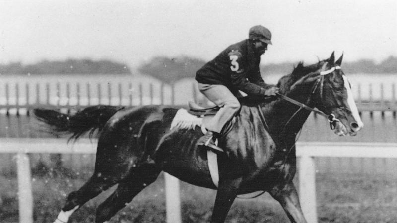 Black and white photo of an African-American jockey riding a horse at high speed.