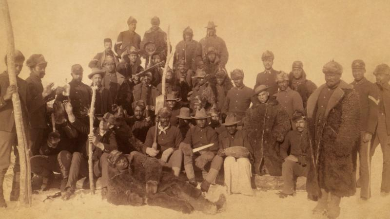 Sepia-colored photo portrait of an African-American infantry unit from the late 19th century.
