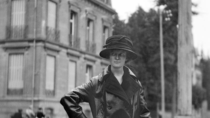 Black and white photo of a woman in an elegant raincoat and hat.