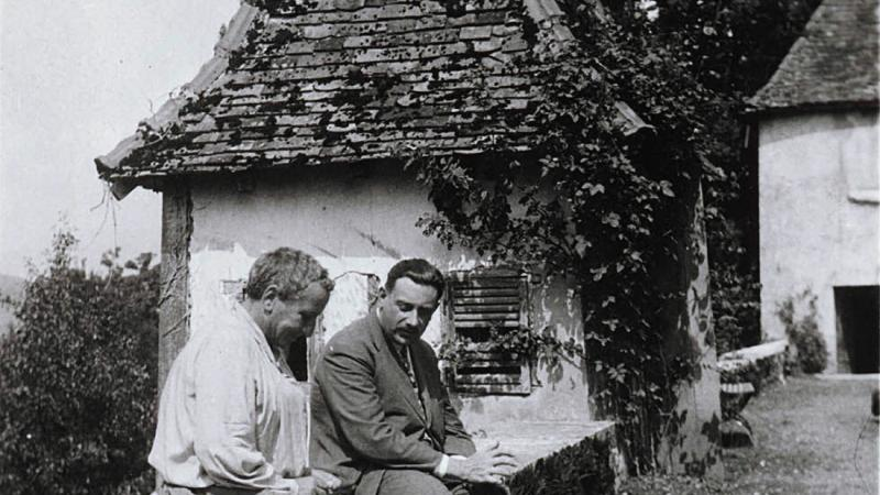 Black and white photo of Gertrude Stein sitting with a male friend on an overlook next to a road.