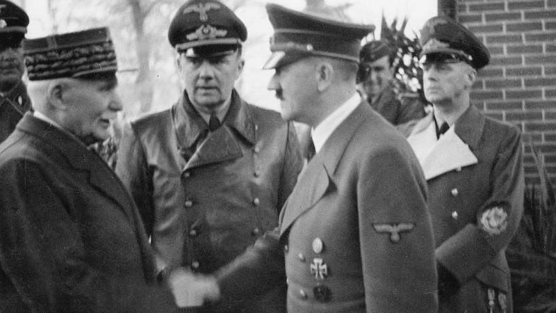 Black and white photo of Marshal Petain and Adolf Hitler shaking hands.