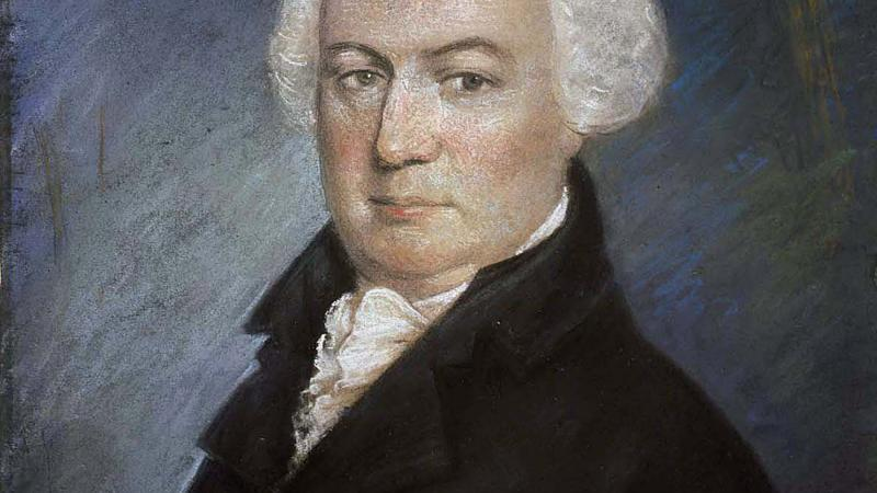 Portrait of a balding man in a black 18th century suit.