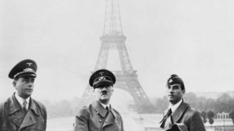 Black and white photo of three military men (including Adolf Hitler) standing in front of the Eiffel Tower.
