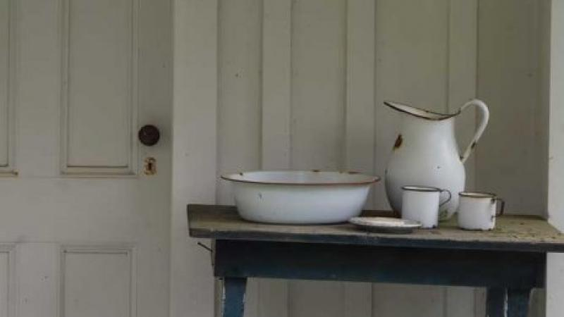 Color photo of a pitcher and two teacups on a table, with an aged wooden door in the background.