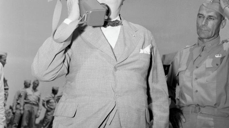 Black and white photo of Winston Churchill holding a large walkie-talkie to his ear.