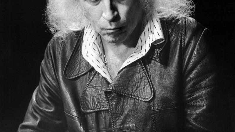 Black and white photo of an aged musician, slightly balded, with long, white, frizzy hair. He wears a leather jacket and collared shirt underneath.