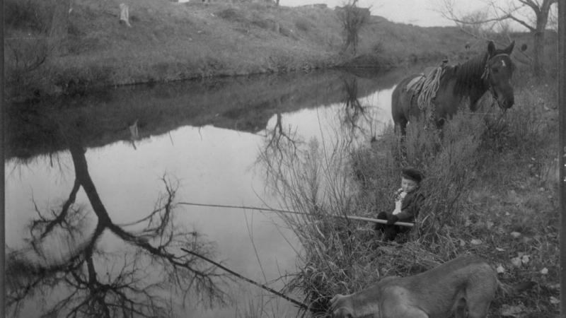 Black and white photo of a little boy fishing in a stream while his dog attempts the same maneuver in the foreground.