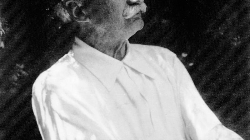 Black and white profile portrait of Jens Jensen wearing a white, short-sleeved shirt.