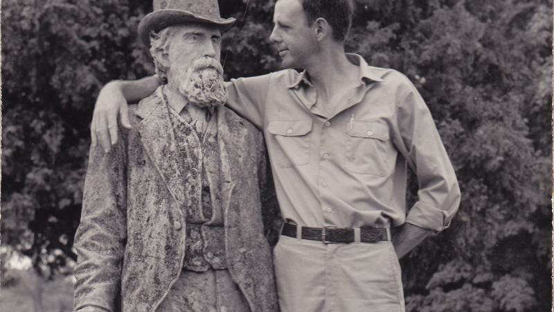 Black and white photo of Wendell Berry putting his arm around the statue of an old man.