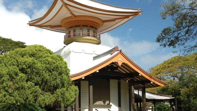 Color photo of a temple with a pagoda amid lush trees.