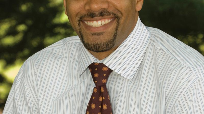 Color photo portrait of Chad L. Williams in a white shirt and burgundy tie.