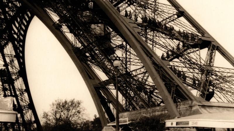 Sepia-colored photo of German soldiers scaling the Eiffel Tower during the occupation of France.