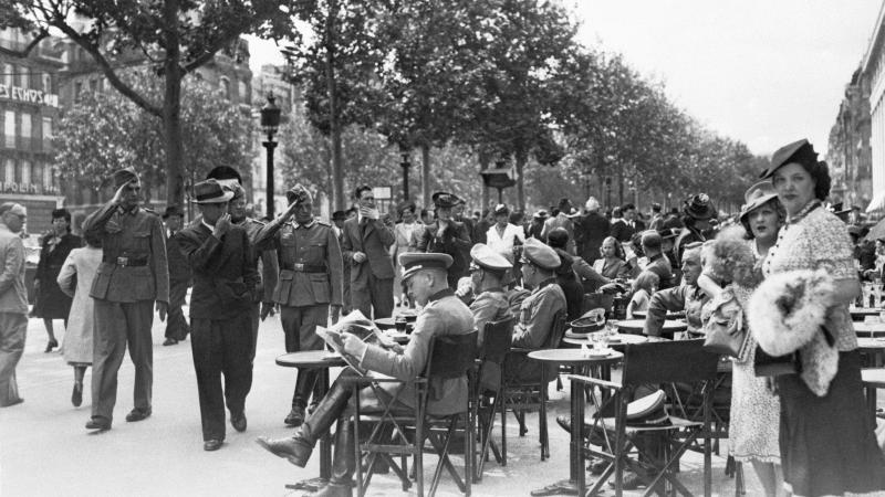 Black and white photo of German soldiers and French civilians sitting in open air cafes in Paris.