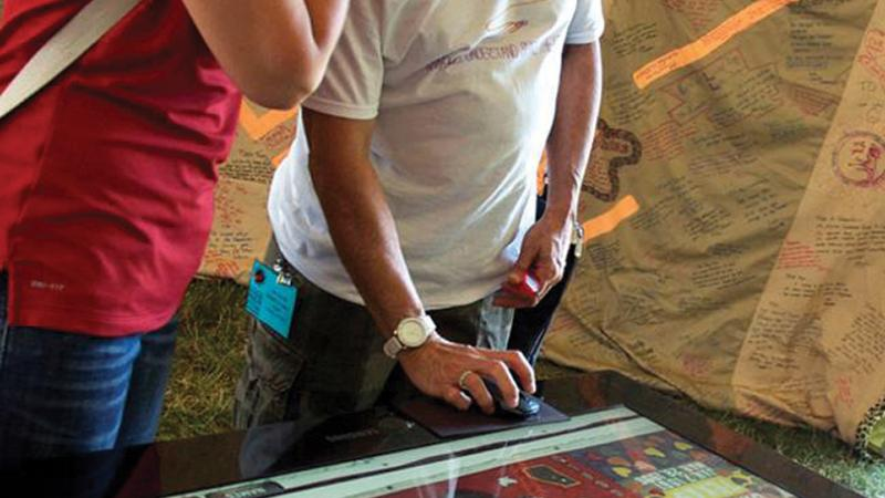 Color photo of two individuals staring down at what looks to be a sort of digital gaming table.