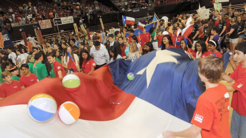 Color photo of a crowd of young students flopping inflatable balls around on top of a large Texas flag.
