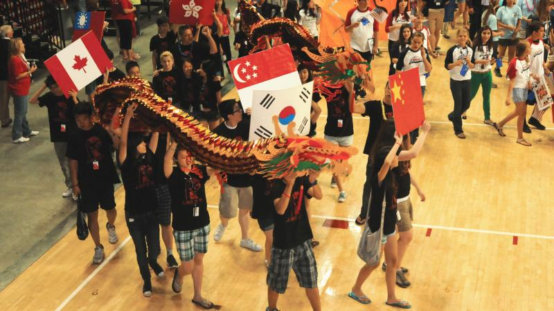 Photo of young students carrying a Chinese dragon and the flags of China, South Korea, and Canada.