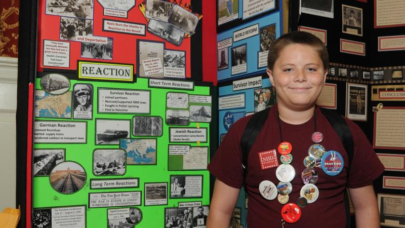 Photo of a young student standing in front of his history exhibit.