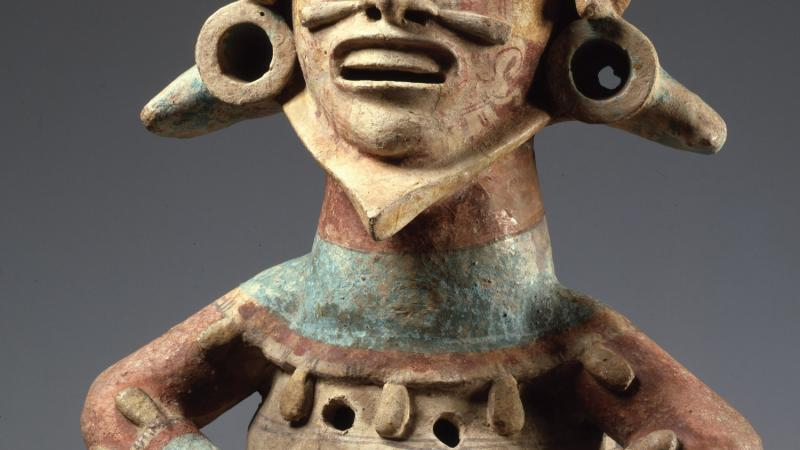 Photo of a Mixtec statue that is sitting with his mouth open, either chanting or laughing.