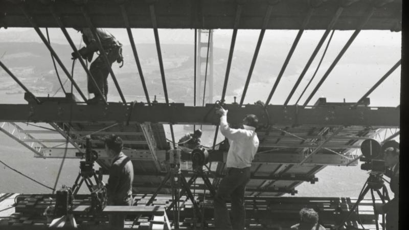Black and white photo of men working on the Golden Gate bridge, high up in the air.