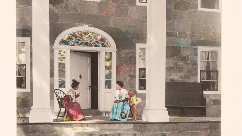 Color illustration of two old ladies conversing on the porch of a large house with front columns.